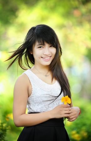 A young Thai woman in park holding a flower